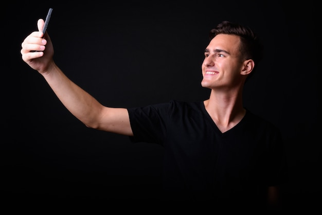 Studio shot di giovane uomo bello su sfondo nero