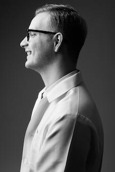 Studio shot di giovane uomo bello medico con i capelli biondi contro il muro grigio in bianco e nero