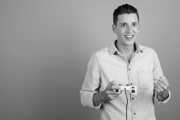 Studio shot di giovane uomo bello giocare contro uno sfondo grigio in bianco e nero