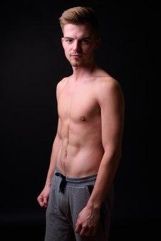 Studio shot di giovane uomo bello a torso nudo su sfondo nero