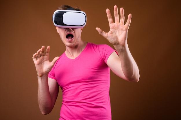 Studio shot di giovane uomo bello che indossa una maglietta rosa con corrispondenti occhiali rosa su sfondo marrone