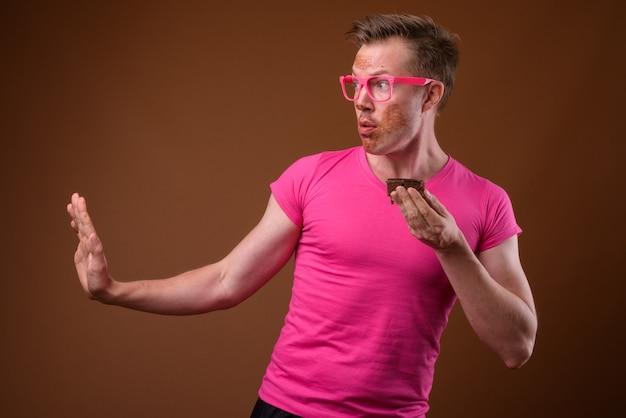 Studio shot di giovane uomo bello che indossa una maglietta rosa con corrispondenti occhiali rosa pur avendo torta al cioccolato su sfondo marrone