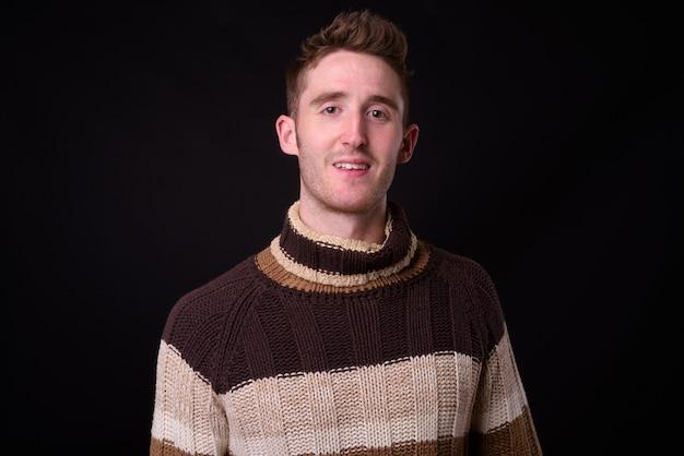 Studio shot di giovane uomo bello con maglione a collo alto pronto per l'inverno su sfondo nero