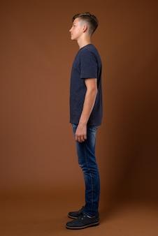 Studio shot di giovane adolescente bello contro backgrou marrone