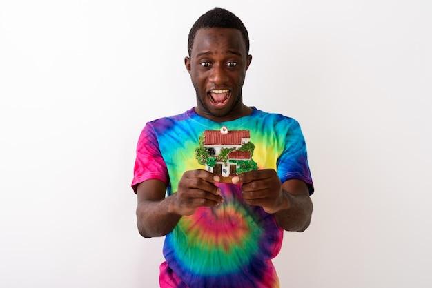Studio shot di giovane felice africano nero uomo che sembra eccitato whi