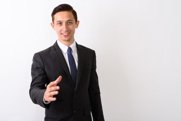 Studio shot di giovane imprenditore felice sorridente mentre dà la mano