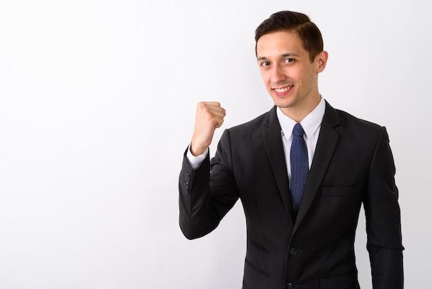 Studio shot di giovane imprenditore felice sorridente mentre guarda mot