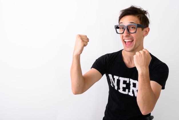 Studio shot di giovane uomo nerd felice sorridente mentre pensa el