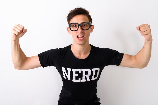 Studio shot di giovane uomo nerd flettendo entrambe le braccia mentre indossa ey