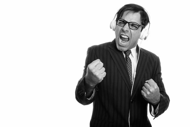 Studio shot di giovane imprenditore persiano ascoltando musica con entrambi i pugni alzati isolati