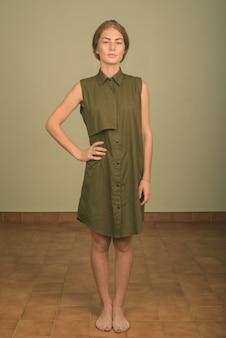 Studio shot della giovane donna che indossa un abito verde senza maniche su colorato