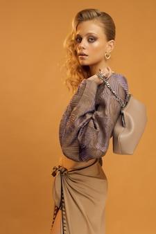 Foto verticale dello studio, modello di donna in abiti alla moda e con una borsa elegante tra le mani, sfondo beige tinta unita. foto di alta qualità