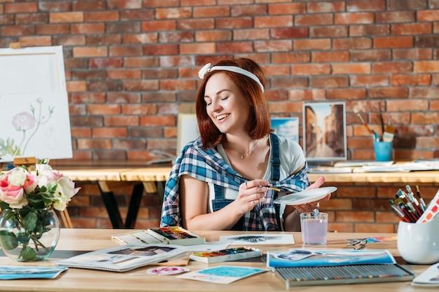 Studio sul posto di lavoro. artista al lavoro. donna sorridente della testarossa che fa pittura ad acquerello. sketchbook e forniture di tavolozza in giro.