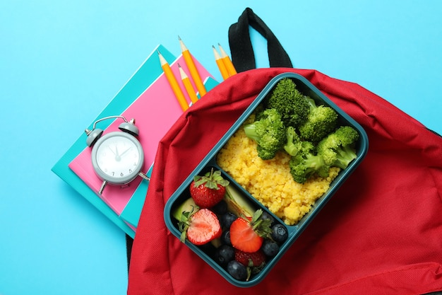 Concetto di studio con scatola del pranzo su sfondo blu