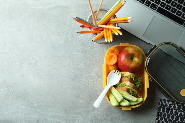 Concetto di studio con scatola del pranzo su tavolo grigio strutturato