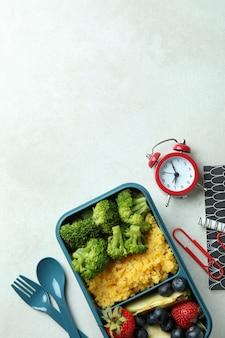 Concetto di studio con scatola per il pranzo su tavolo bianco strutturato Foto Premium