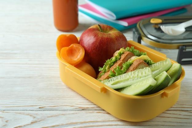 Concetto di studio con scatola del pranzo sul tavolo di legno bianco