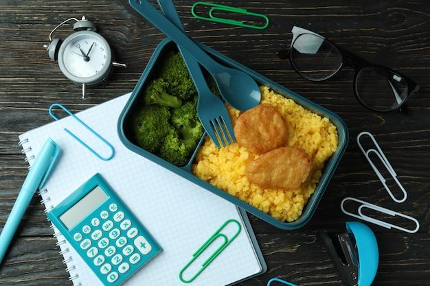 Concetto di studio con scatola del pranzo sul tavolo di legno