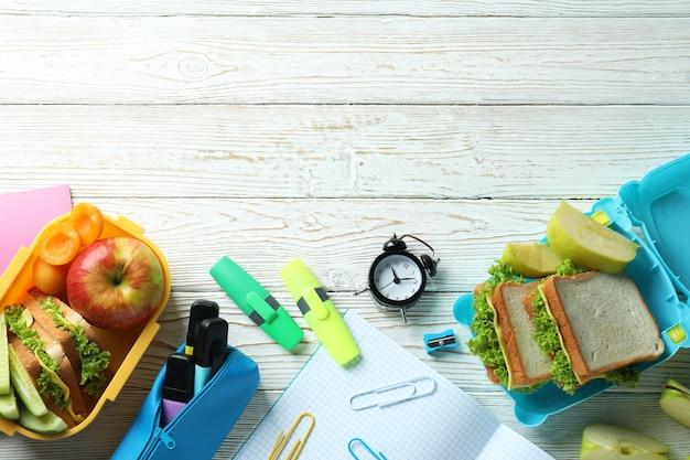 Concetto di studio con scatole per il pranzo su un tavolo di legno bianco