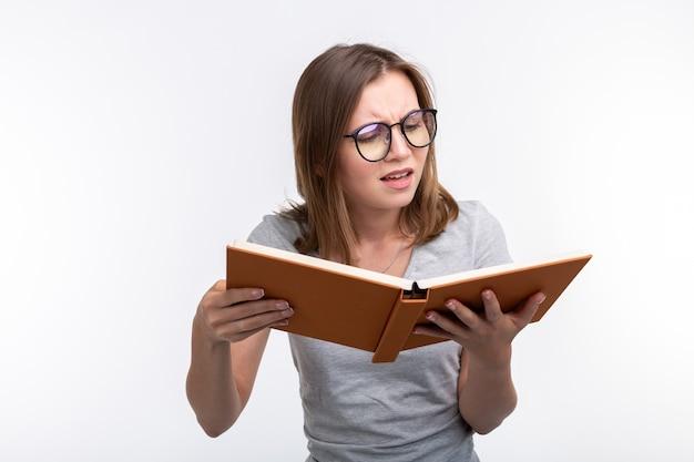 Studiare il concetto di persone di educazione. studentessa è stanca di imparare le lezioni che è in camicia grigia