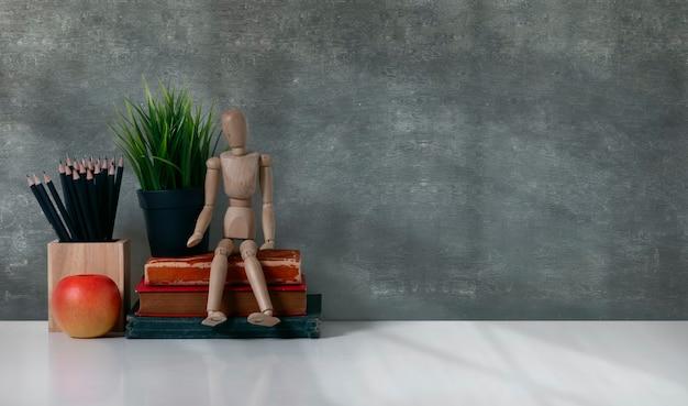 Tavolo da studio con copia spazio, libri, matita, pianta d'appartamento e figura in legno sulla parete della lavagna