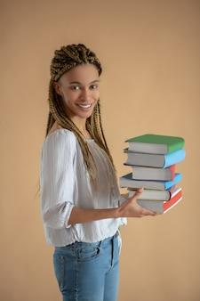 Processo di studio. felice giovane donna afroamericana portando una pila di libri davanti a lei, sorridendo