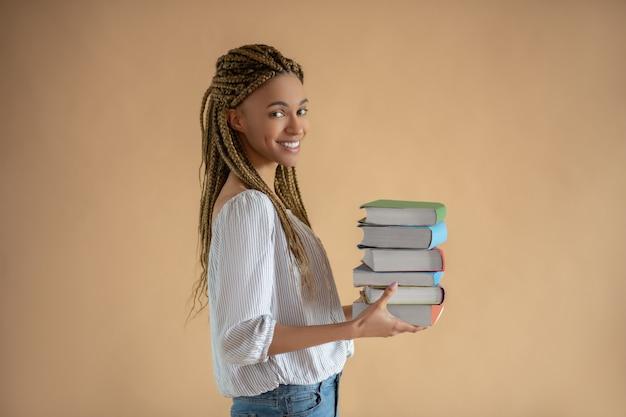 Processo di studio. felice giovane donna afro-americana che trasportano pila di libri davanti a lei