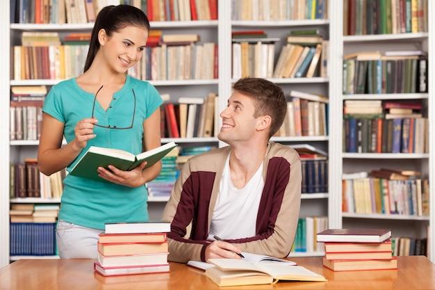 Studiare insieme. allegro giovane seduto alla scrivania mentre una bella donna in piedi vicino a lui e con in mano un libro