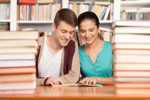 Studiare insieme. allegro giovane uomo e donna seduti vicini l'uno all'altro alla scrivania della biblioteca e leggendo un libro