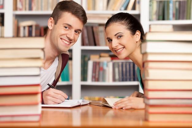 Studiare insieme. allegro giovane uomo e donna seduti alla scrivania della biblioteca e guardando fuori dalle pile di libri