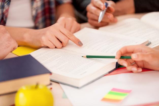 Studiare insieme. primo piano di studenti che puntano un libro seduti insieme alla scrivania