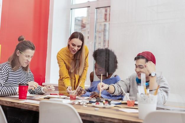 Studiare insieme. quattro giovani studenti di talento del dipartimento artistico si sentono gioiosi studiando insieme
