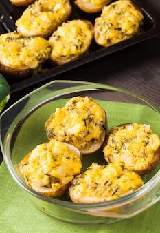 Patate al forno ripiene con uova, formaggio e spezie