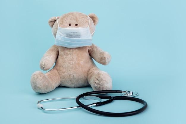 Animale di peluche orso in maschera con stetoscopio isolato sull'azzurro. concetto di assistenza sanitaria per bambini