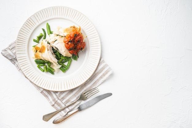 Carne di pollo farcita con filo set, con pomodorini al forno e fagiolini, su pietra bianca