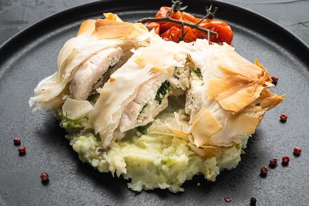 Carne di pollo farcita con filo set, con pomodorini al forno, purè di patate, su pietra nera