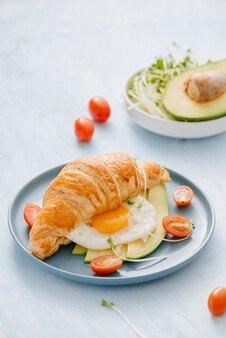 Croissant farcito con avocado, uovo di frittata e verdura fresca