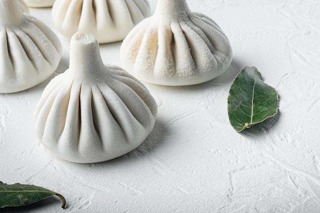Gnocchi ripieni, manti di pasta e set tritato, su superficie di pietra bianca