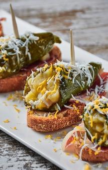 Spiedino di peperoni verdi ripieni e prosciutto iberico con scaglie d'uovo