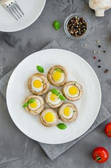 Funghi ripieni con uova di quaglia su un piatto bianco con basilico e foglie di timo su uno sfondo di cemento scuro. antipasto di pasqua.