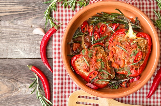 Peperoni rossi ripieni con salsa di pomodoro piccante e rosmarino in piatto di argilla al rustico in legno