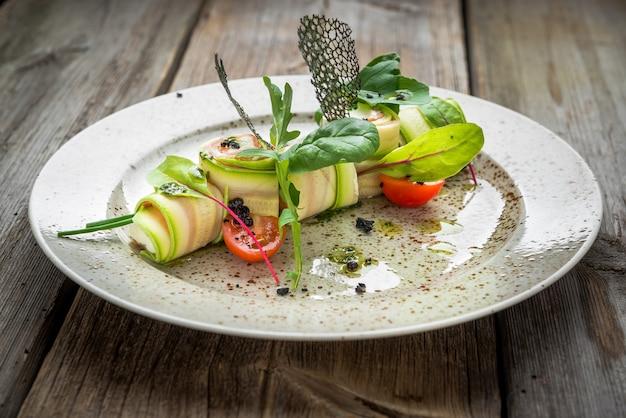 Zucchine ripiene arrotolate con crema di formaggio su sfondo complesso, su uno sfondo di legno