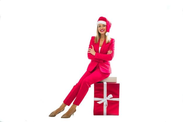 Stulish donna con cappello di natale si siede su una grande scatola rosa, immagine isolata