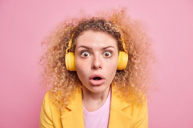 La giovane donna emotiva sbalordita con i capelli ricci ascolta musica tramite le cuffie tiene gli occhi aperti non può credere in notizie scioccanti indossa abiti eleganti isolati sul muro rosa. oddio concetto.