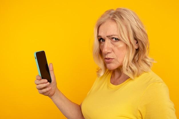 Telefono frustrato sbalordito della tenuta della donna isolato. cattivo concetto di cellulare.