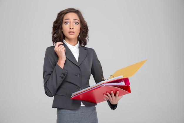 Donna d'affari piuttosto riccia e scioccata sbalordita in costume grigio che tiene documenti in raccoglitori