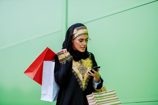 Splendida donna araba in abbigliamento tradizionale che cammina all'aperto con le borse della spesa in mano e digitando o leggendo un messaggio su smart phone generazione millenaria.