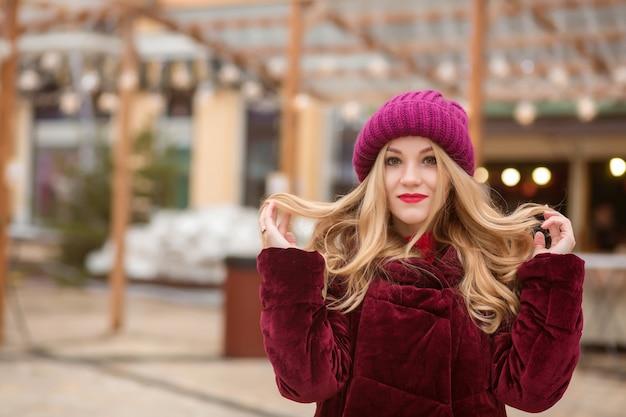 Splendida donna bionda che indossa abiti invernali caldi, in posa sullo sfondo delle luci