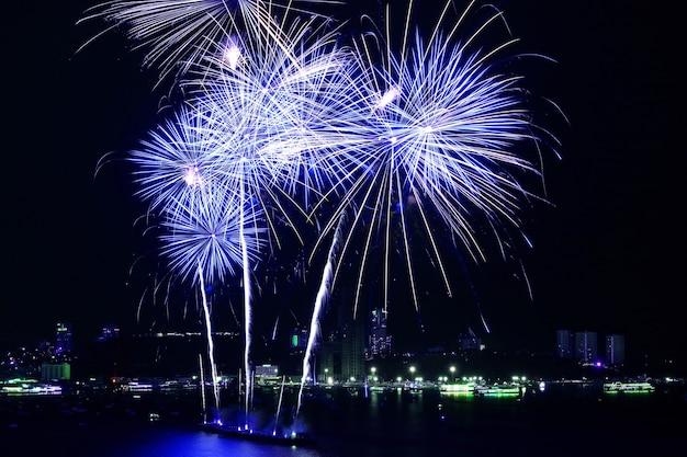 Stupendi fuochi d'artificio blu e bianchi che esplodono nel cielo notturno sopra la baia