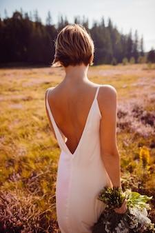 Splendida sposa che attraversa il campo dei fiori viola